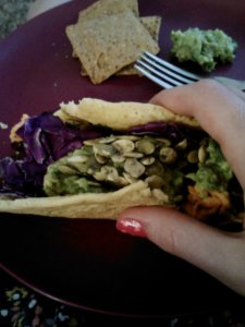 Socca-style taco filled with raw red cabbage, black beans, sweet potato, homemade guac and sprouted pumpkin seeds.
