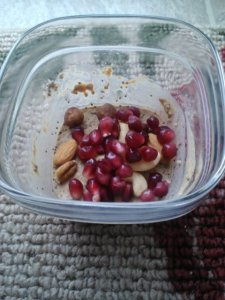 Protein chia pudding topped with pom seeds and raw mixed nuts.