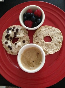 Bagel thins topped with coconut butter and stevia chocolate chips. Side of Sunwarrior protein 'frosting' and berries.